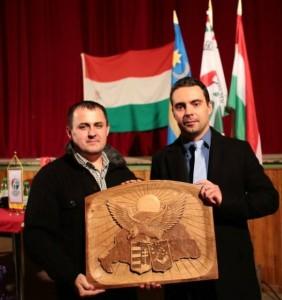 Peter Waum (stânga), unul dintre inițiatorii asociației HVIM România, îi oferă o sculptură cu Harta Ungariei Mari liderului Jobbik, Vona Gabor.