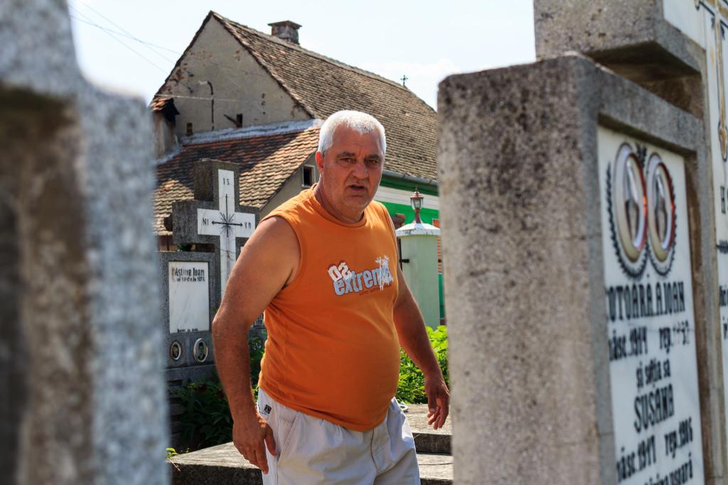 Aurel Poșa, rătăcind printre crucile cimitirului din Porumbacu de Jos, în căutarea mormântului lui Eliseu Ghenea. FOTO: Sergiu Brega.