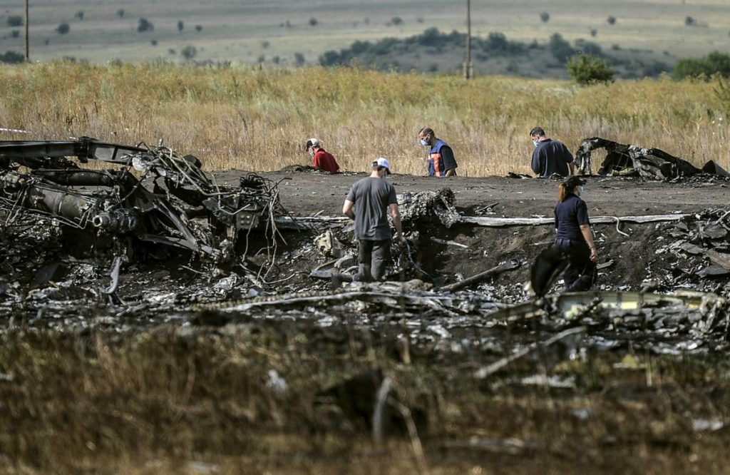 Anchetatorii investighează locul unde s-a prăbușit avionul MH17 al companiei aeriene Malaysia Airlines, lângă satul Hrabove (Grabovo), la 80km de Donetsk, în 25 iulie 2014. Foto: BULENT KILIC AFP PHOTO/ MEDIAFAX