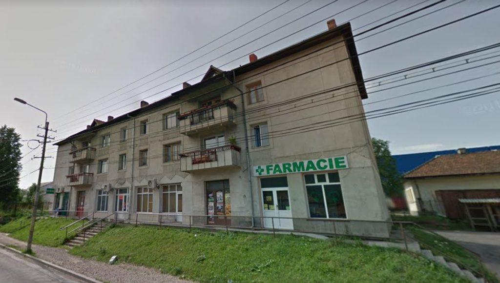 """Farmacia din imagine, Ilacrisfarm SRL, e printre puținele din România care a fost închisă în urma anulării, în instanță, a autorizației de funcționare - emise, în 2011, sub semnătura ministrului Cseke Attila. Deși fusese deschisă la parterul acestui bloc din orașul Câmpulung Moldovenesc (județul Suceava), ea primise voie să funcționeze mințind că își va desfășura activitatea într-un """"centru comercial"""". FOTO: Google Street View."""