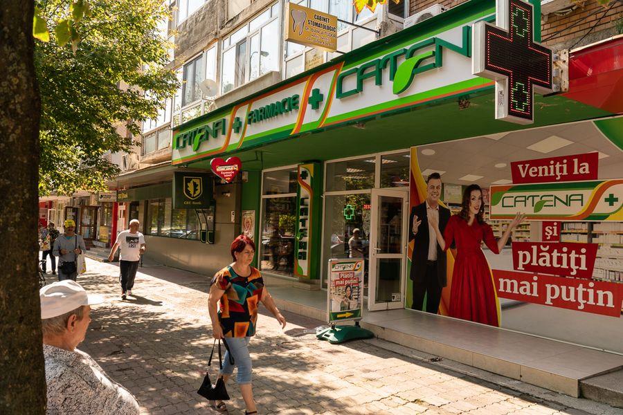 """În aceeași zi în care Ministerul Sănătății a acordat farmaciei Hyperici autorizația de funcționare pentru localul din spatele primăriei, lanțul Catena a primit, de asemenea, dreptul de a-și deschide două farmacii în Târgoviște, tot cu alibiul că vor funcționa în incinta unor """"centre comerciale"""". În realitate, ele se găsesc fie la un parter de bloc (în imagine), fie într-un magazinaș din piața de legume și fructe """"Bărăției"""". FOTO: Sergiu Brega."""