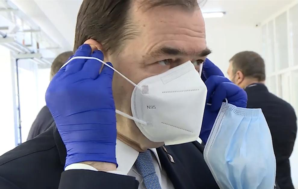 Premierul României probează o mască N95 produsă la Dragomirești. Sursă: Guvernul României - captură Youtube